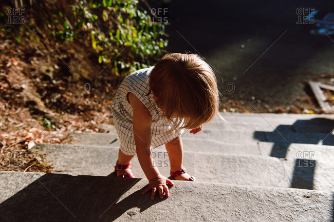 Toddler climbing up steps outside