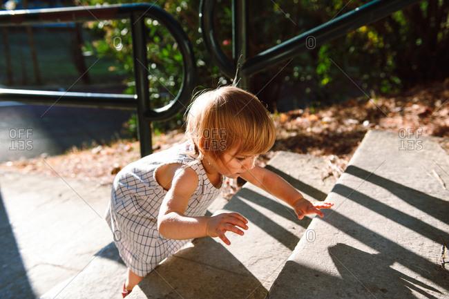 Little girl climbing up stone steps