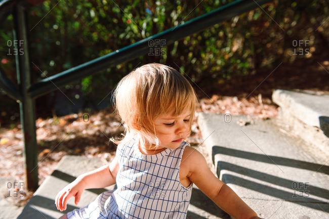 Young girl sitting on steps at golden hour