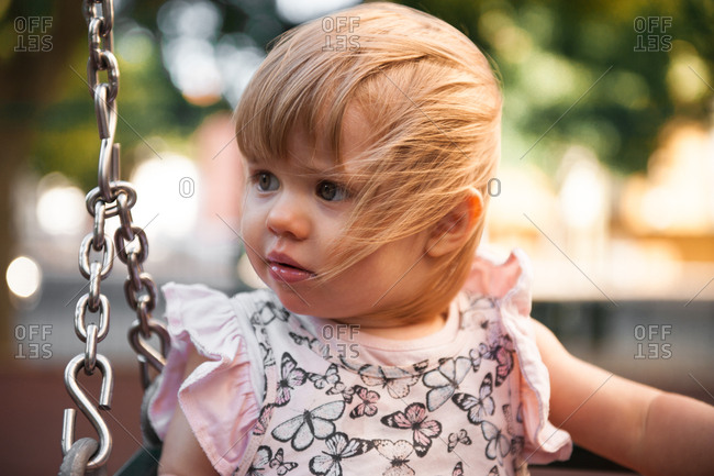 Toddler sitting on swing in the breeze