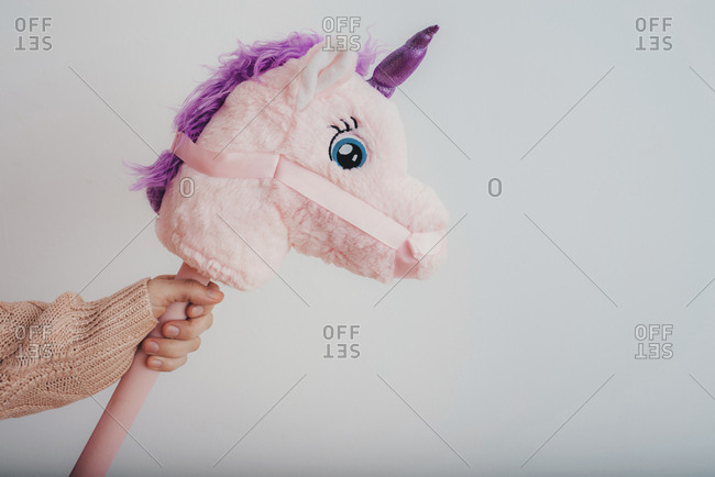 Child hand holding stuffed unicorn on a stick