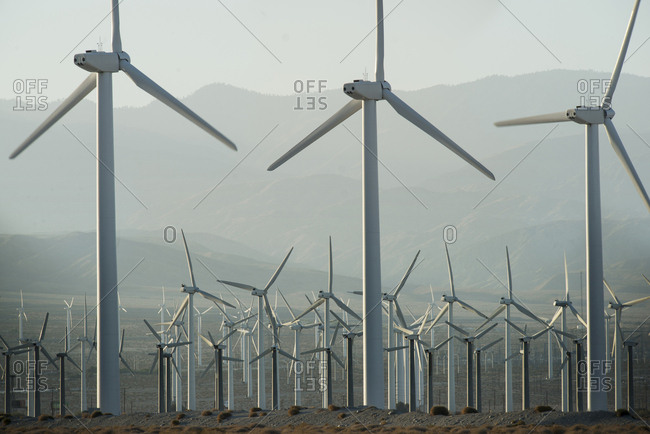 USA, California - May 1, 2013: View of windmills on field against mountains