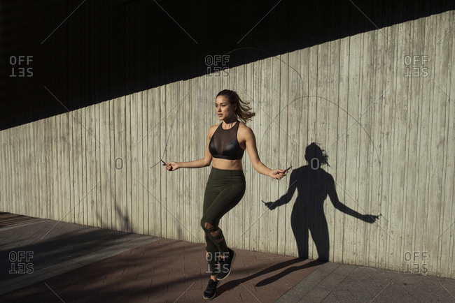Young woman skipping while exercising against wall