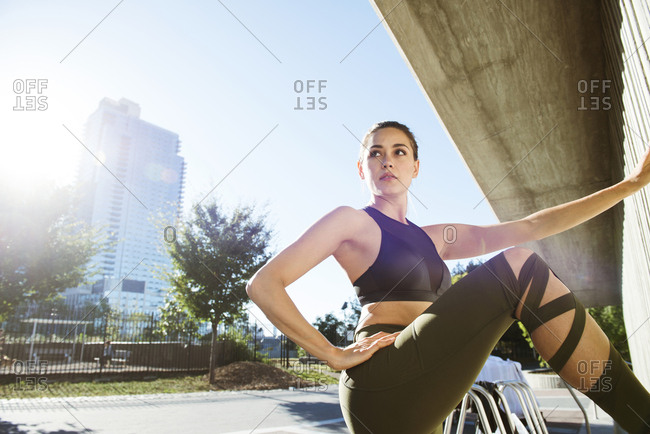 Confident young woman exercising during sunny day in city