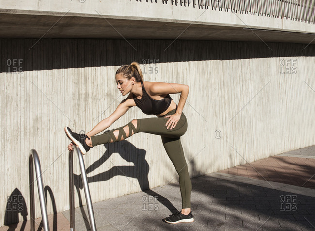 Side view of young woman stretching leg on metal against wall