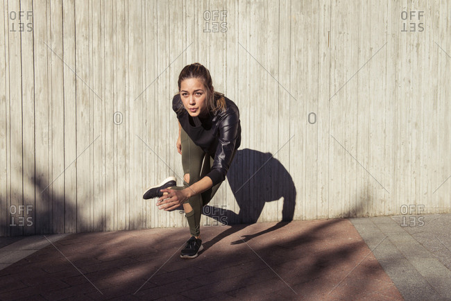 Determined young woman exercising against wall during sunny day