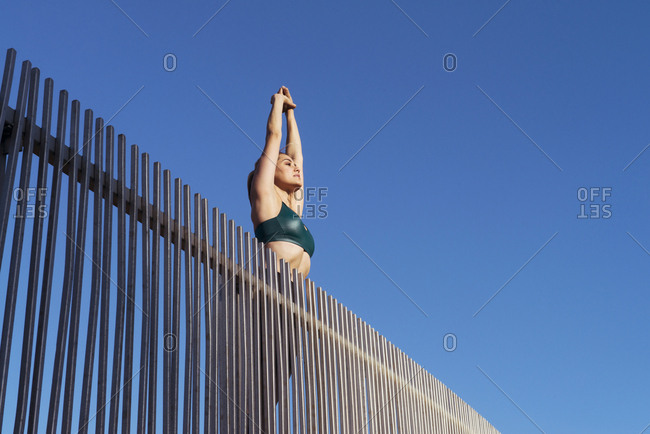 Low angle view of young woman stretching arms while exercising on bridge against clear sky