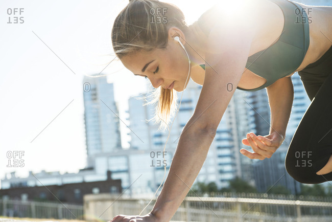 Young woman exercising while listening music in city