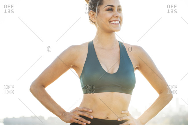 Cheerful young woman with hands on hip wearing sports bra against clear sky