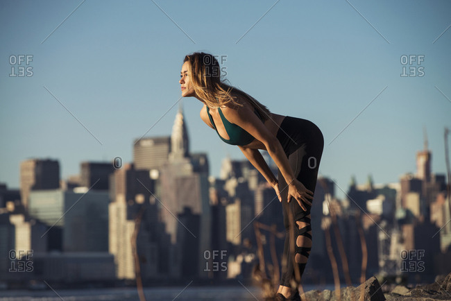 Side view of young woman exercising against cityscape and clear sky