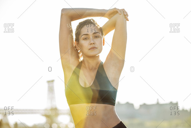 Portrait of confident young woman stretching arms while exercising against bridge during sunny day in city
