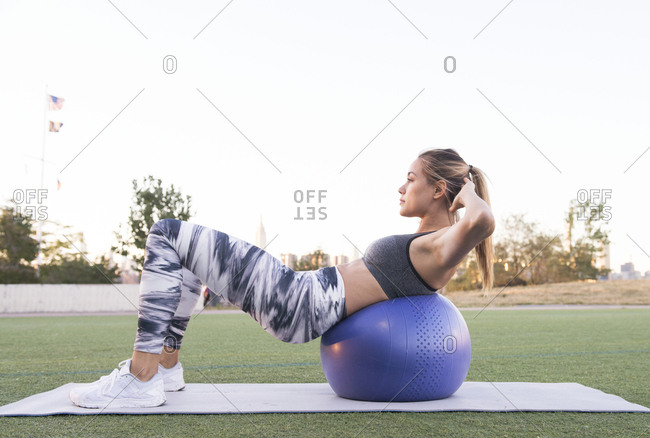 Side view of young woman with hands behind head exercising on fitness ball against clear sky at park