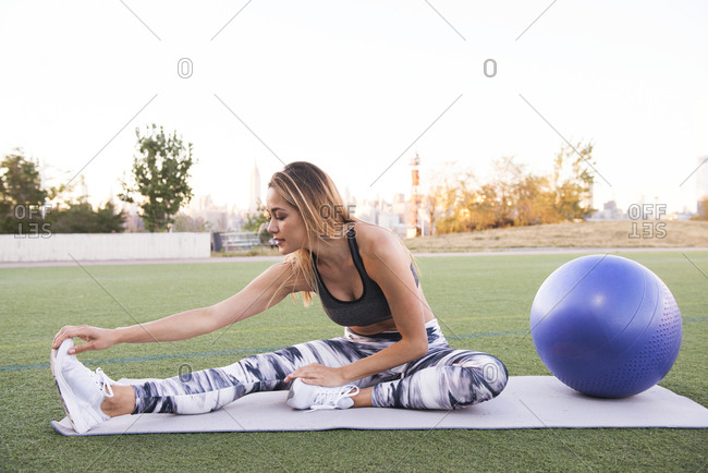 Full length of young woman stretching while sitting on exercise mat by fitness ball against clear sky at park