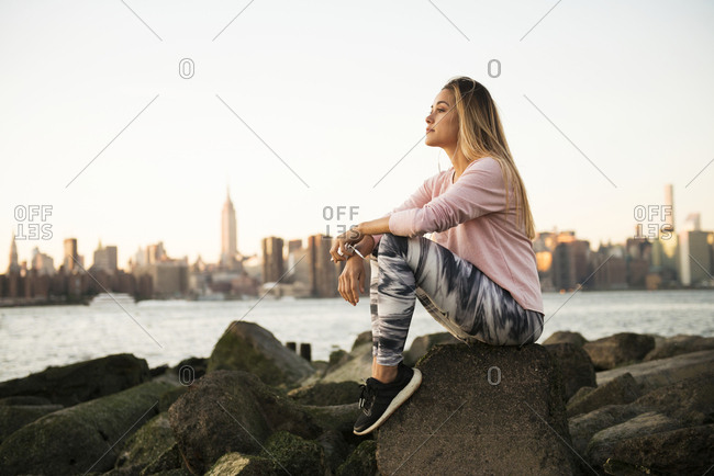 Side view of thoughtful young woman sitting on rock by river against cityscape and clear sky