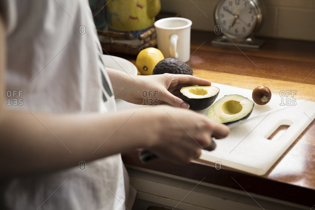 Midsection of woman cutting avocado at kitchen