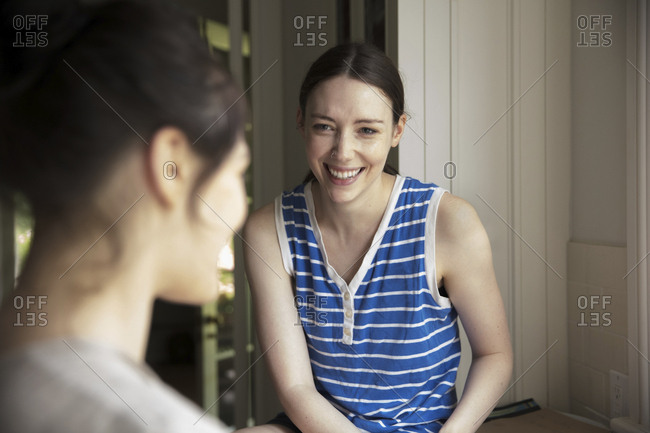Cheerful woman looking at female friend in kitchen
