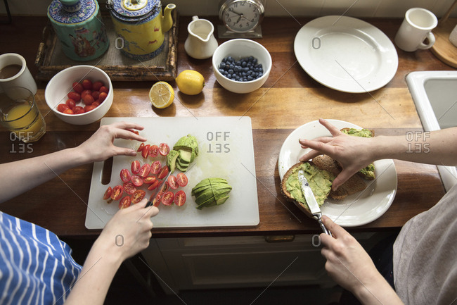 Cropped image of female friends preparing food in kitchen