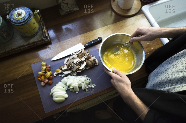 Cropped hands of man mixing egg in bowl at kitchen
