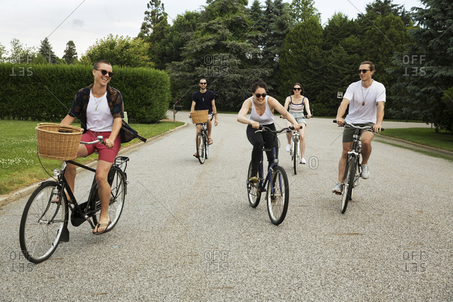 Cheerful friends riding bicycles on road at park