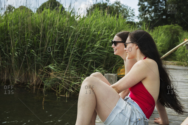 Happy female friends looking away while sitting on pier over lake