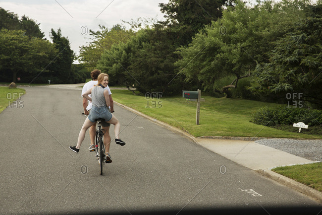 Rear view of friends riding bicycles on road at park