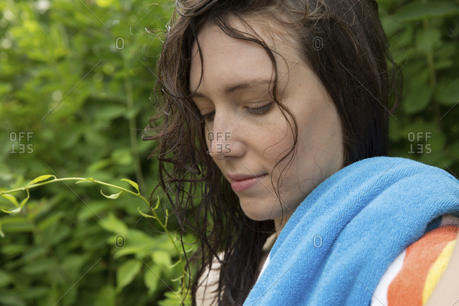 Close-up of thoughtful young woman with towel against plants