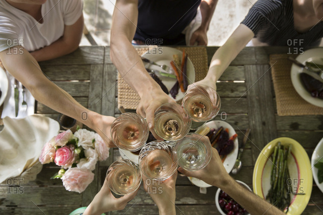 Cropped hands of friends toasting drinks at dining table