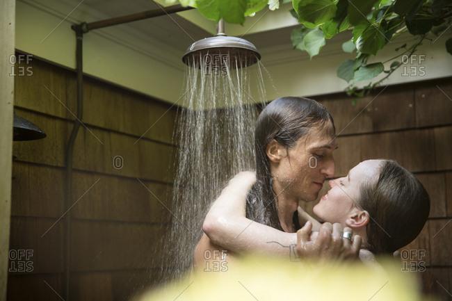Loving couple taking bath under shower at backyard