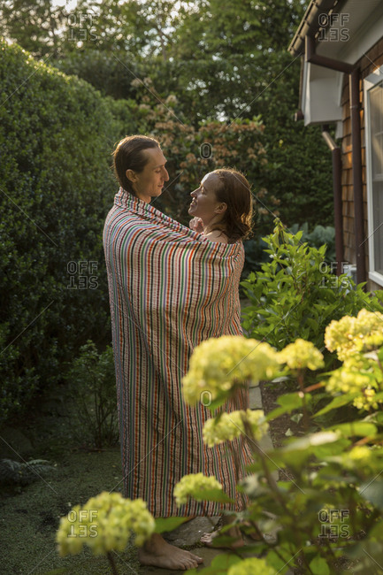 Side view of loving couple standing at backyard while being wrapped in blanket