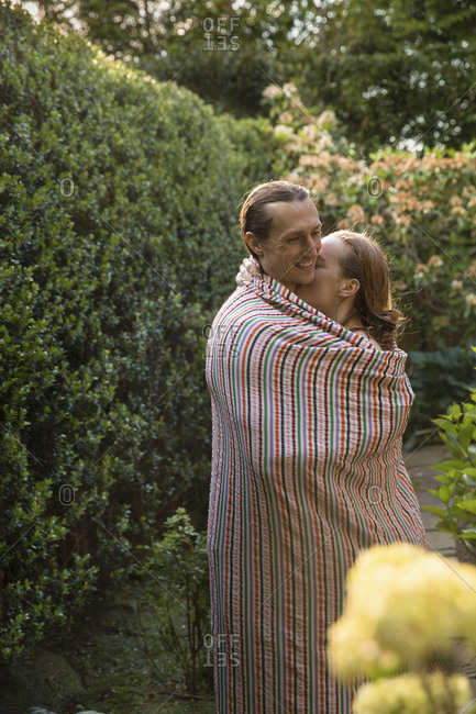 Side view of loving girlfriend embracing boyfriend at backyard while being wrapped in blanket