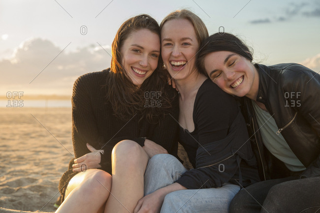 Portrait of happy female friends sitting at beach against sky during sunset