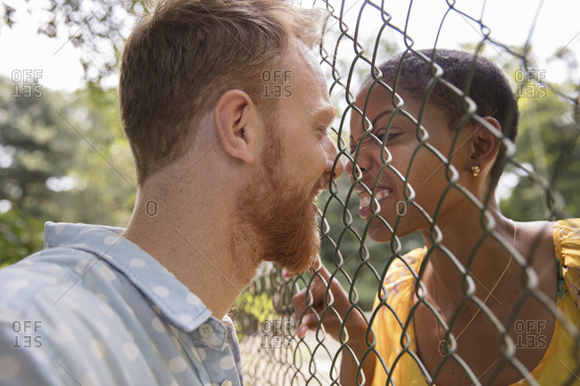 Happy couple looking at each other through fence at park