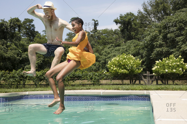 Happy couple jumping into swimming pool against sky at tourist resort