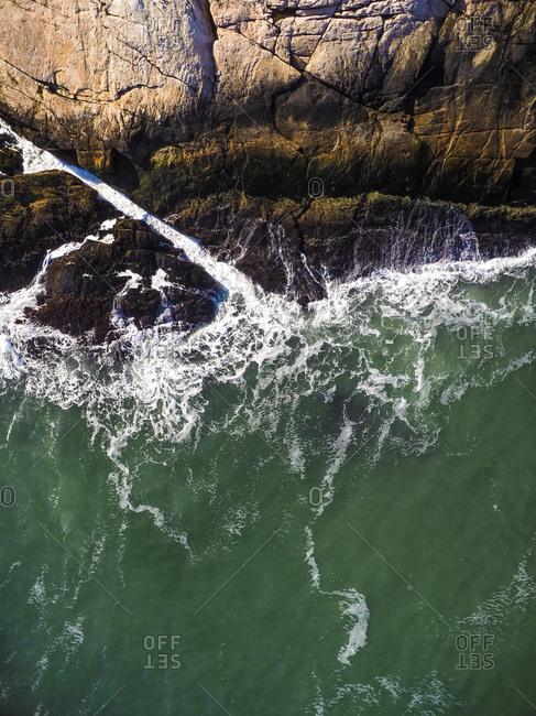 High angle view of waves splashing on rocks at beach