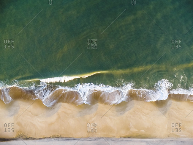High angle idyllic view of waves splashing on shore at beach