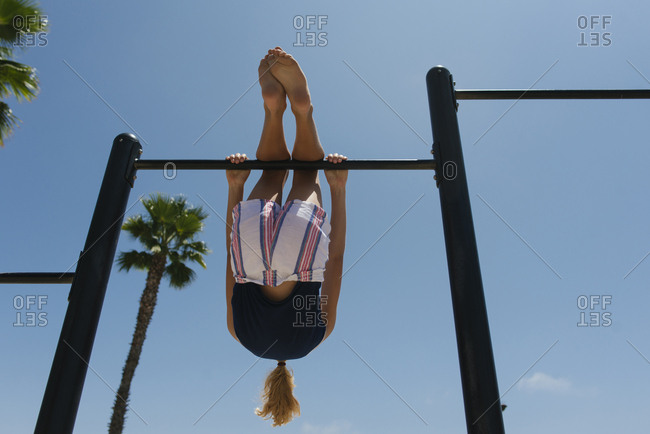 Low angle view of girl playing on play equipment at park against sky