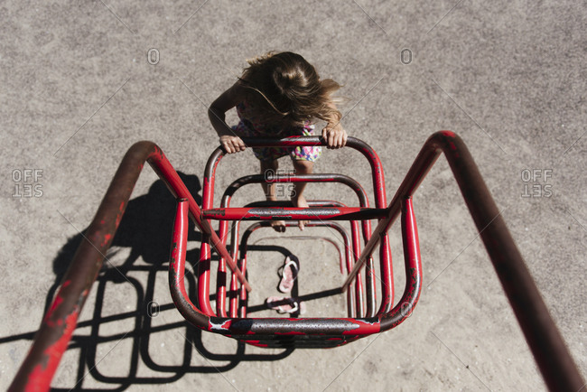 High angle view of girl climbing on metallic structure at park