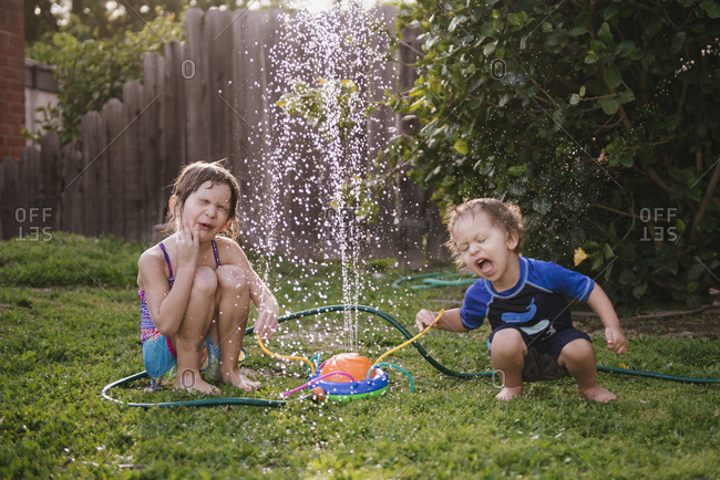 Siblings playing by fountain in yard