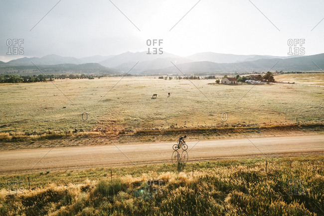 High angle view of man riding bicycle on dirt road against sky