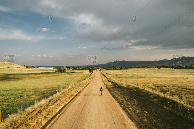 Rear view of man riding bicycle on dirt road against cloudy sky