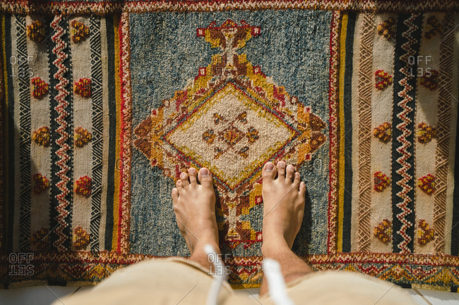 Low section of man standing on traditional rug