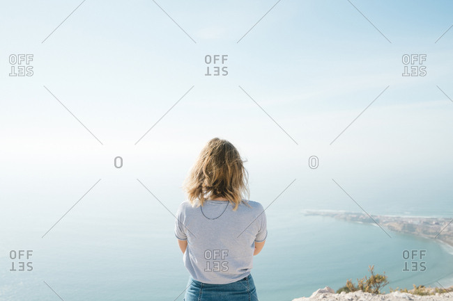 Woman looking at view while standing against sea and sky during sunny day