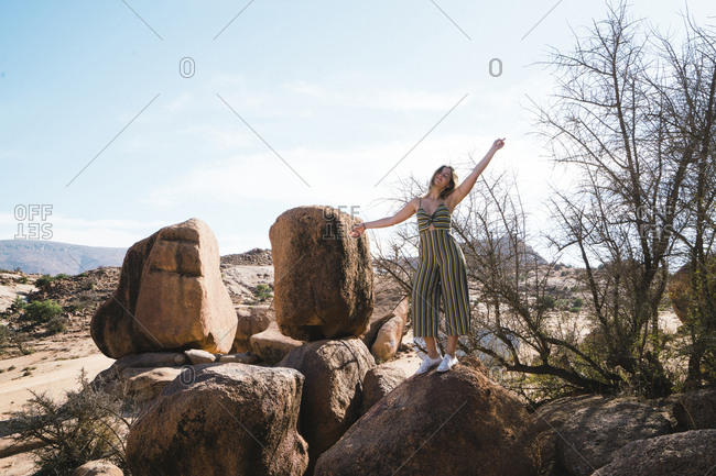 Carefree woman standing on rock against sky at desert