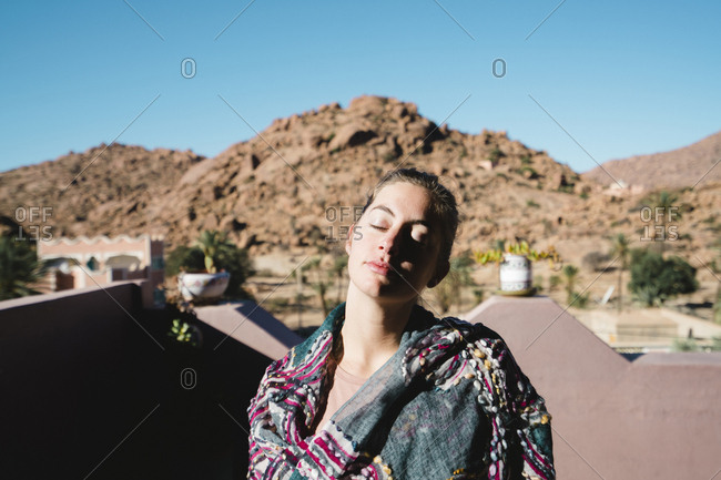 Woman with eyes closed standing against mountains on terrace during sunny day
