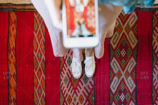 Low section of woman photographing with smart phone while standing on traditional rug