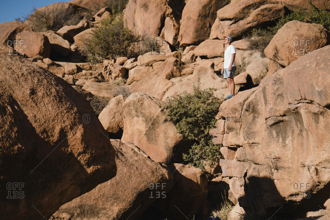Full length of man looking at view while standing on rocks at desert during sunny day