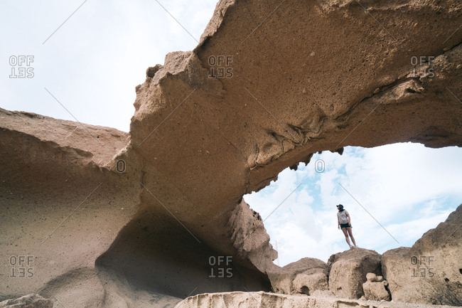 Low angle view of woman standing on rock formation against sky