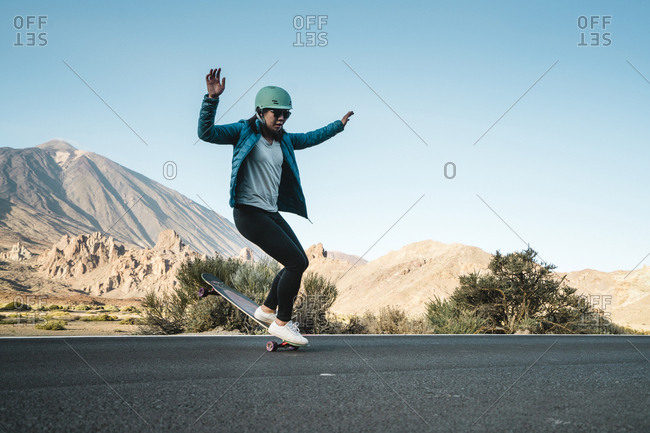 Woman performing stunt on skateboard against mountains