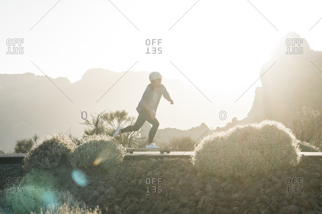 Full length of woman skateboarding against clear sky during sunny day