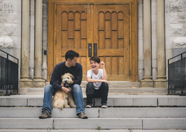 Father with dog looking at cheerful son sitting against door on steps